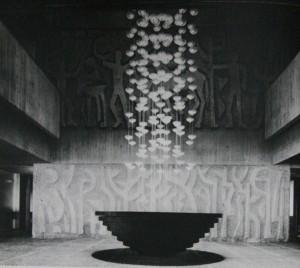 建築家自身がデザインしたエントランスのシャンデリア。後ろは洋画家 伊藤研之デザインによる石壁レリーフ。